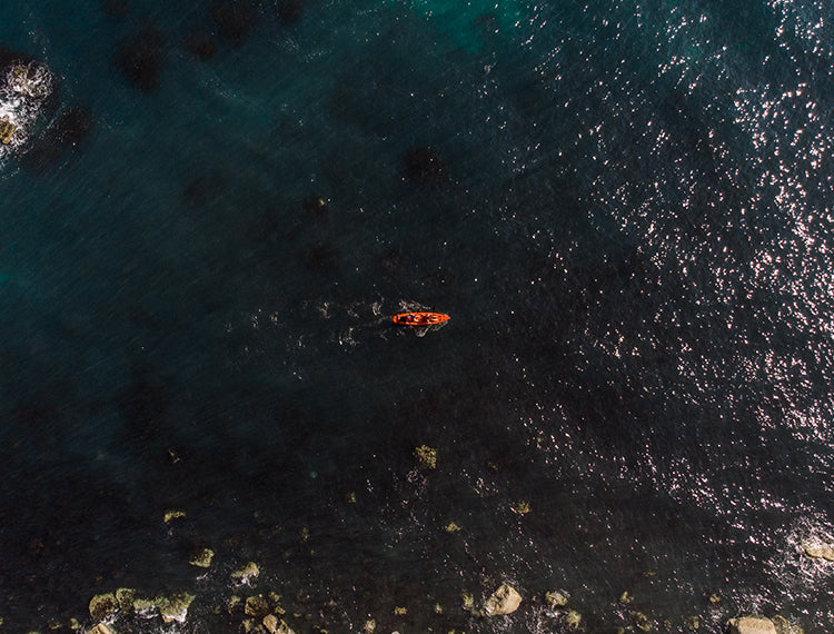 A Panned Out Shot Of Someone Sea Kayaking
