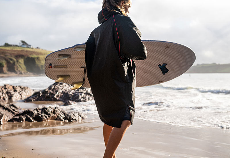 walking to the water wearing Red Original Women's Short Sleeve Pro Change Robe - Black with Grey Lining