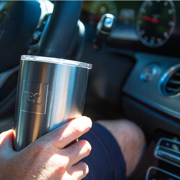 Man in a car holding an insulated Travel Cup