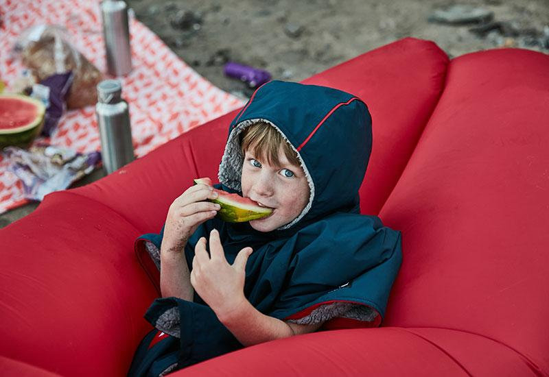 Boy wearing kids changing robe eating a watermelon
