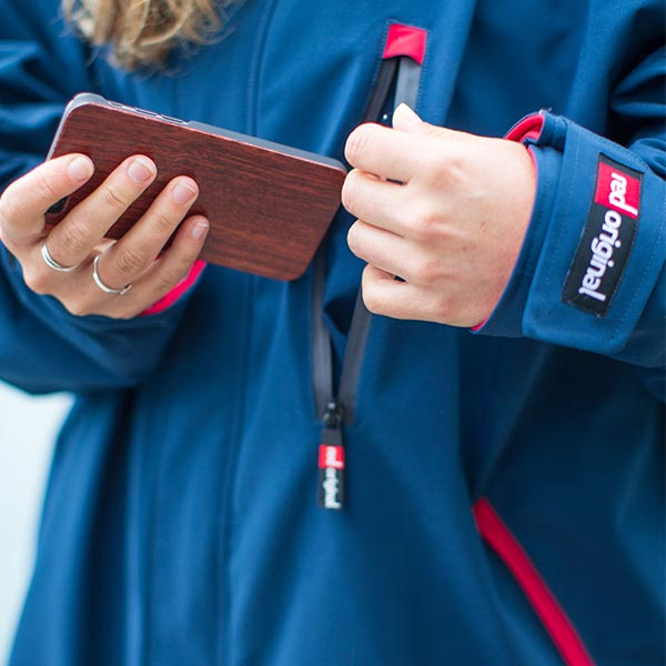 Woman putting a mobile phone in a waterproof jacket pocket
