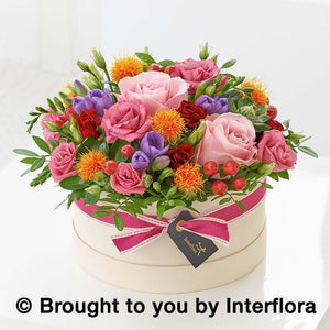 Seasonal flowers of pinks, cerise, reds, orange and lilacs. Designed in a hatbox