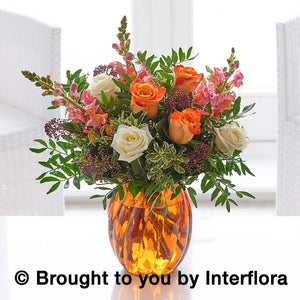Orange and cream roses with autumnal foliage flowers arranged in an orange vase