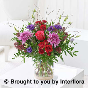Seasonal Autumnal flowers in vase. Dark pink, purple and red flowers, loosely tied
