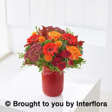 Seasonal Autumnal flowers in reds and oranges arranged in a red vase