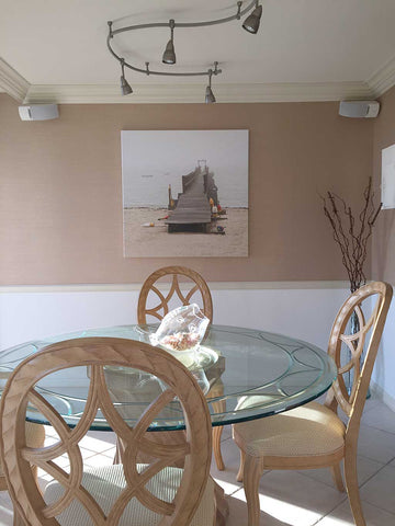 Foggy Dock artwork by Martha Everson Photography compliments the light wood furniture in this dinningroom.