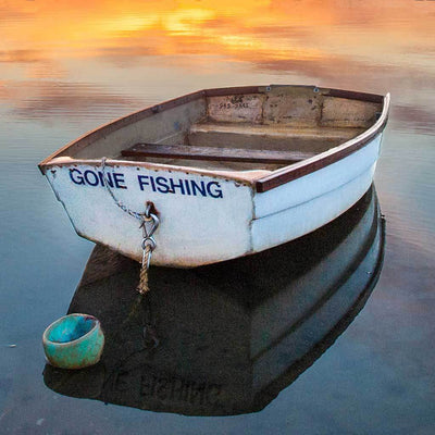 Stern view of the  Gone fishing rowboat at anchor with orange sunset sky reflected in the water