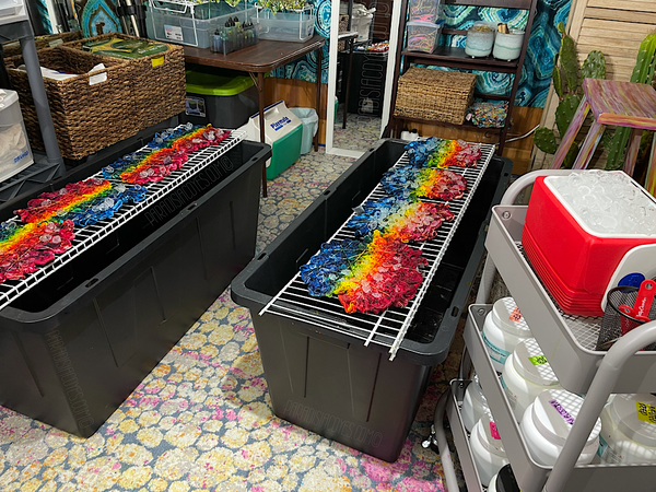 A closer up look at the two large splat racks that reside in front of the tie dye bar. There are rainbow splatters ice dyeing in progress, and a rolling cart with a mini cooler of ice and other supplies on the bottom right side of the frame