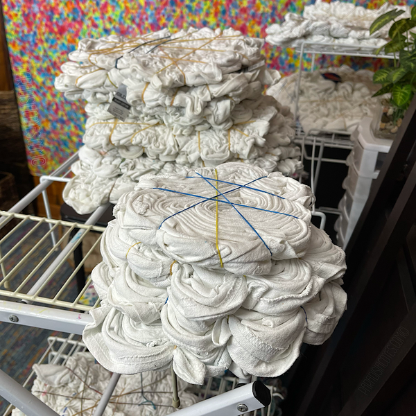 A stack of pre-tied, rubber-banded splatter pattern shirts, a stash of tees are always kept tied and ready to dye for custom tie dye requests