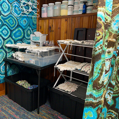 The far right wall of the area just to the right of the tie dye bar, with an aqua teal geode design tapestry on the wall and a table in front with piles of pre-tied, ready to dye blank tops and tees. Above the table is a shelf built in to the wall from the 1950's, which stores all of my doubles and 5lb fiber reactive dyes