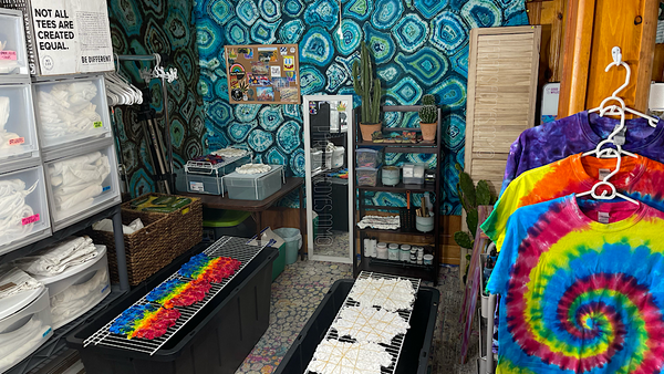 Another angle of the area in front of the tie dye bar, with a teal and blue geode tie dye tapestry on each wall and rainbow splatter ice dyes in progress on the splat rack bins.