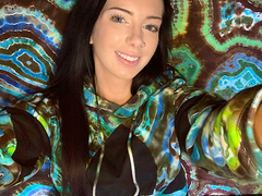 A selfie of tie dye artist, Rhiannon Cloud, wearing a geode pattern tie-dyed Adidas pullover hoodie whilst laying against a geode pattern tie dye fitted bed sheet in a similar blue, teal and brown color scheme.