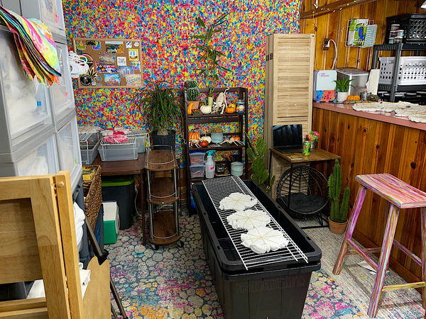 Looking at the tie dye studio and bar from dead center, to the left are drawers full of blank tops prepped and ready to just tie then dye, with a shelf of shipping boxes below. Behind these shelves is a square table in the corner, to the right of that is a bookshelf holding tie dyeing tools and supplies. On the right side of the frame is the bar area, in front of the bar on the floor are large plastic totes with wire shelving placed on top for tie dyeing.