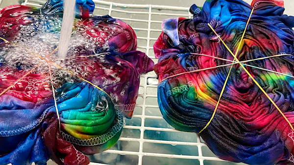 Two confetti spiral ice dye t-shirts being rinsed of excess dye before being washed with Synthrapol in a tub sink