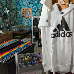 An Adidas hoodie awaiting being tied into geodes with sinew is hanging from a hanger on the right side of the frame, looking beyond it to the main area in front of the tie dye bar. There are two large bins with wire racks on top for tie dyeing, with aqua blue geode tie dye tapestries on each wall