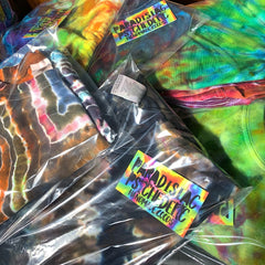 An up-close shot of finished tie dye t-shirts folded and packaged in clear poly t-shirt bags with a business card inside of each