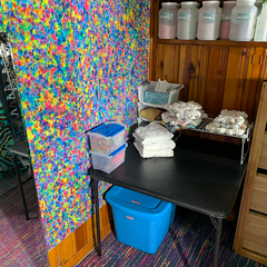 In the area to the right of the bar is a shelf built-in to the wall, which holds all of my backup doubles of dye colors as well as 5lb fiber reactive dye jars. Below that is another square table used for tying fabric into patterns. On the wall is a rainbow splatter pattern tie dye tapestry.