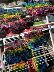 A folding rack of tie dyed Midnight Marbled Rainbow splatter ice dye tees, in the background out of focus are splat racks with more tie dye in progress