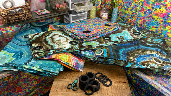 Grommet style curtain panels laid flat on a desk, with vibrant, colorful rainbow splatter tapestries on the two walls behind