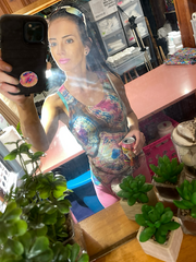 A mirror selfie of tie dye artist, Rhiannon Cloud, behind the bar, wearing a pastel geode tie dye tank top with a purse and sunglasses to match.