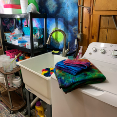 The tub sink with a spiral design shirt awaiting rinsing, to the right is the washer with rainbow tie dye towels folded on top.
