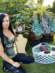 Tie dye artist, Rhiannon Cloud, in front of a tropical fig tree with wicker baskets, t-shirt mannequins on top that are wearing custom made geode tie dye tank tops. Taking photos of the tanks before shipping to later use on a blog or social media.