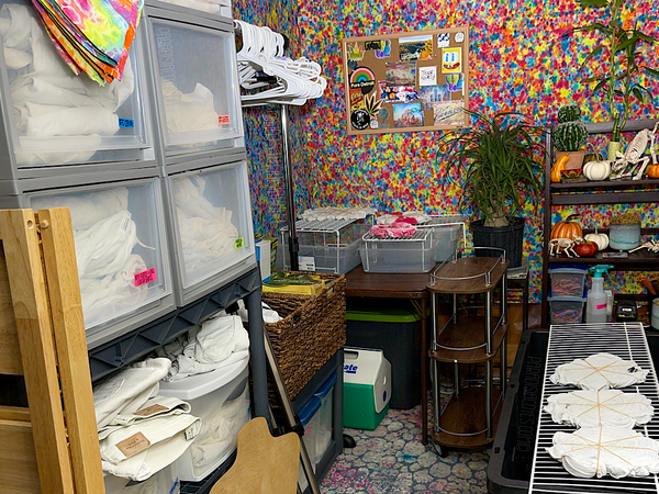 The very left side, far wall of the area in front of the tie dye bar. The speckled rainbow crinkle tie dye tapestry on the wall behind the shelving, clothing rack and dyeing bins gives the room a pop of color