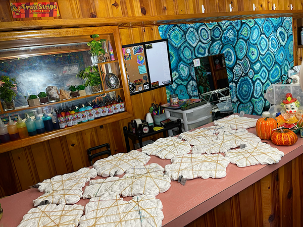 Standing directly in front of the bar, at the end near the wall looking down it toward the area with the built-in wall cubby. On top of the bar are shirts rubber-banded into symmetrical mindscape designs, being prepared to ice dye ahead of Mindscape Monday