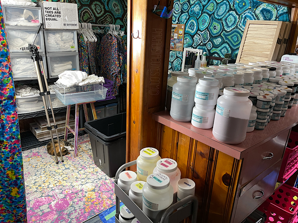 Standing at the end of the tie dye bar, looking toward the studio area just in front of the bar. From here you see a rolling cart with containers of dye, a rainbow tie dye curtain panel hanging in the far left of the frame. Directly ahead are the splat racks, with the shelving, drawers, table and mirror behind it. And of course, a vibrant tie dye tapestry on each wall to give the basement a pop of color