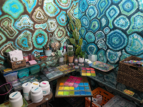 Tie dye studio desk area with page protectors filled with color coordinated dye swatch sample squares, with a rolling cart full of Dharma dye jugs and two blue and teal geode tapestries on each wall