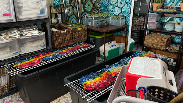 In the area in front of the tie dye bar are 2 large plastic bins with wire closet shelving on top are used as splat racks for tie dyeing. With Teal blue geode pattern tie dye tapestries on each wall.