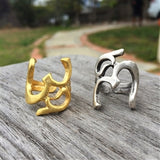 Adjustable Om Symbol Rings shown in Gold and Silver Finish