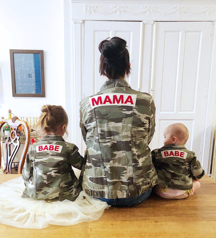 Mom and daughters wearing matching camo jackets.