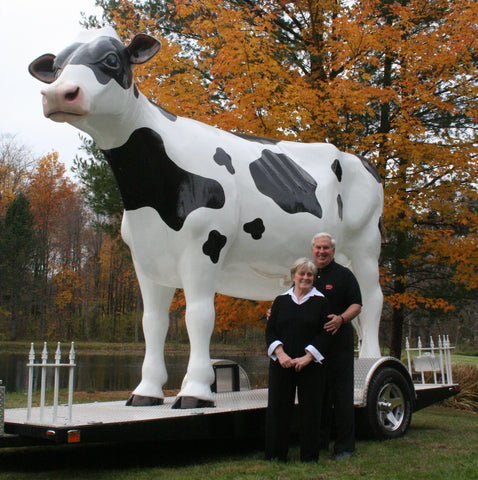 a photo of the Kennedys standing next to a large cow statue