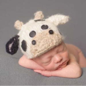 a photo of a baby sleeping with a cow inspired winter hat