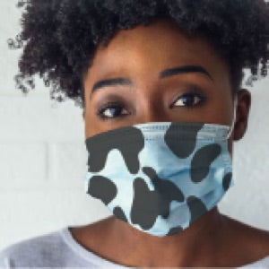 a photo of an African American woman wearing a face mask modeled after the black and white pattern seen on cows