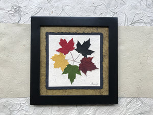 the tattoo pressed maple leaf artwork with green handmade paper and a black frame