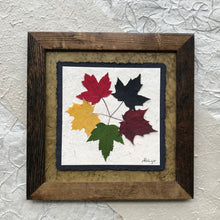 the tattoo; pressed maple leaf artwork with green handmade paper and brown frame