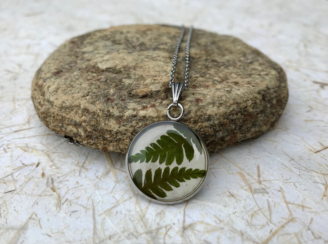 pressed fern pendant sealed in eco resin; stainless steel circle pendant