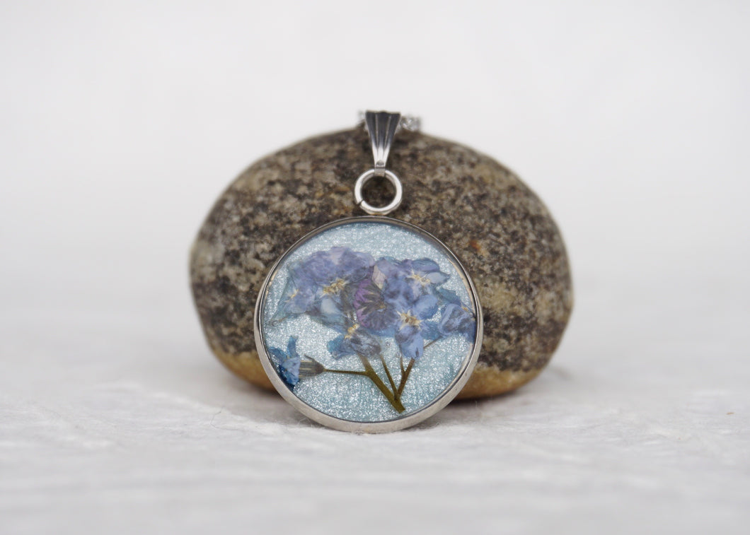 pressed forget me not flower pendant necklace with blue background