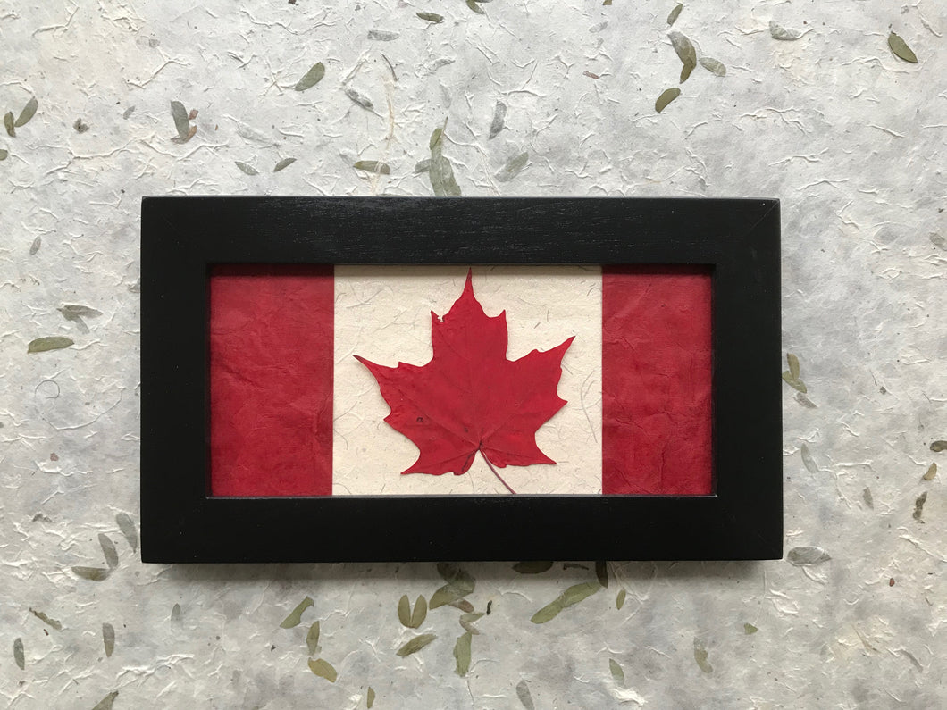 maple leaf in canadian flag design in black frame; handcrafted in canada