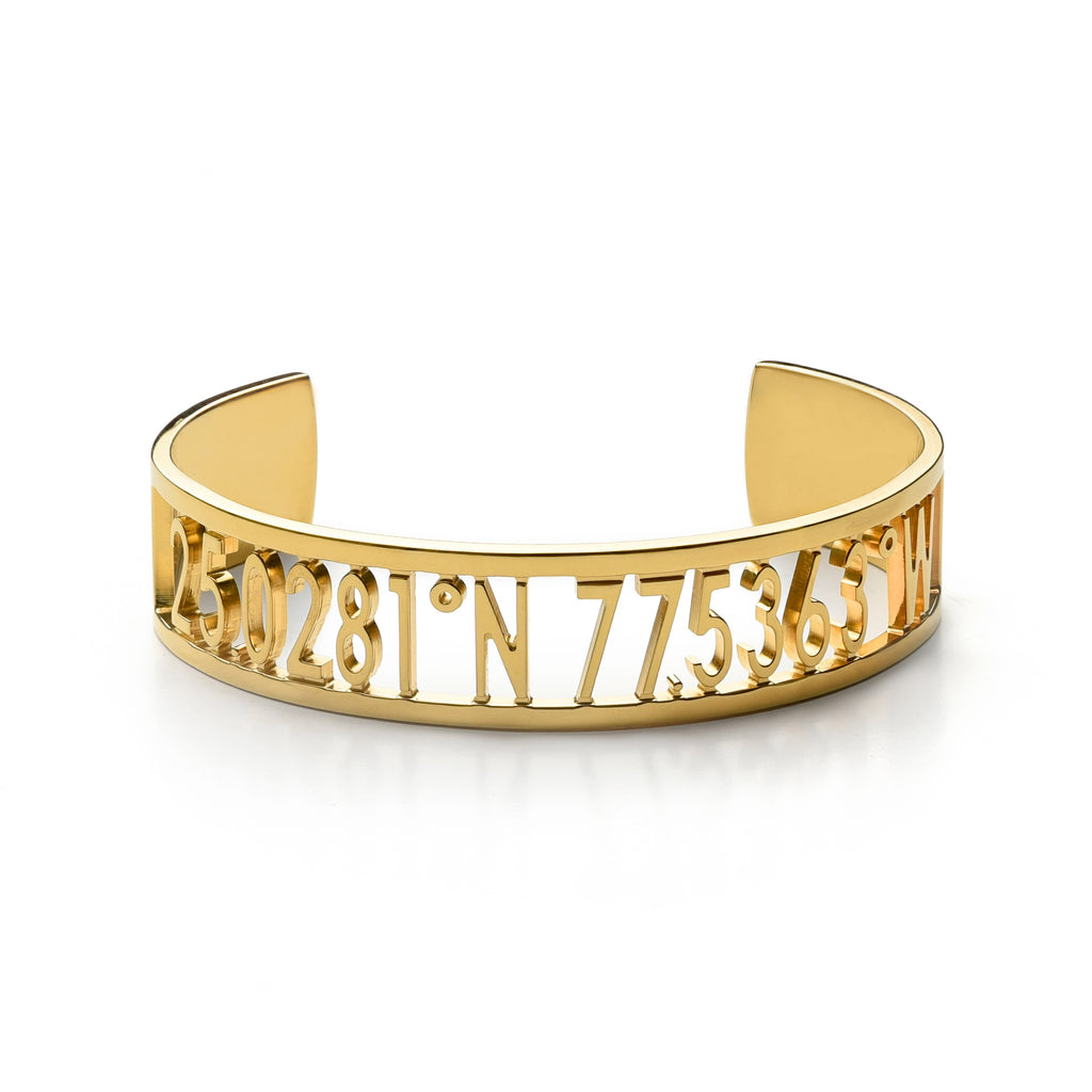 A thick gold cuff bracelet with carved out inscription
