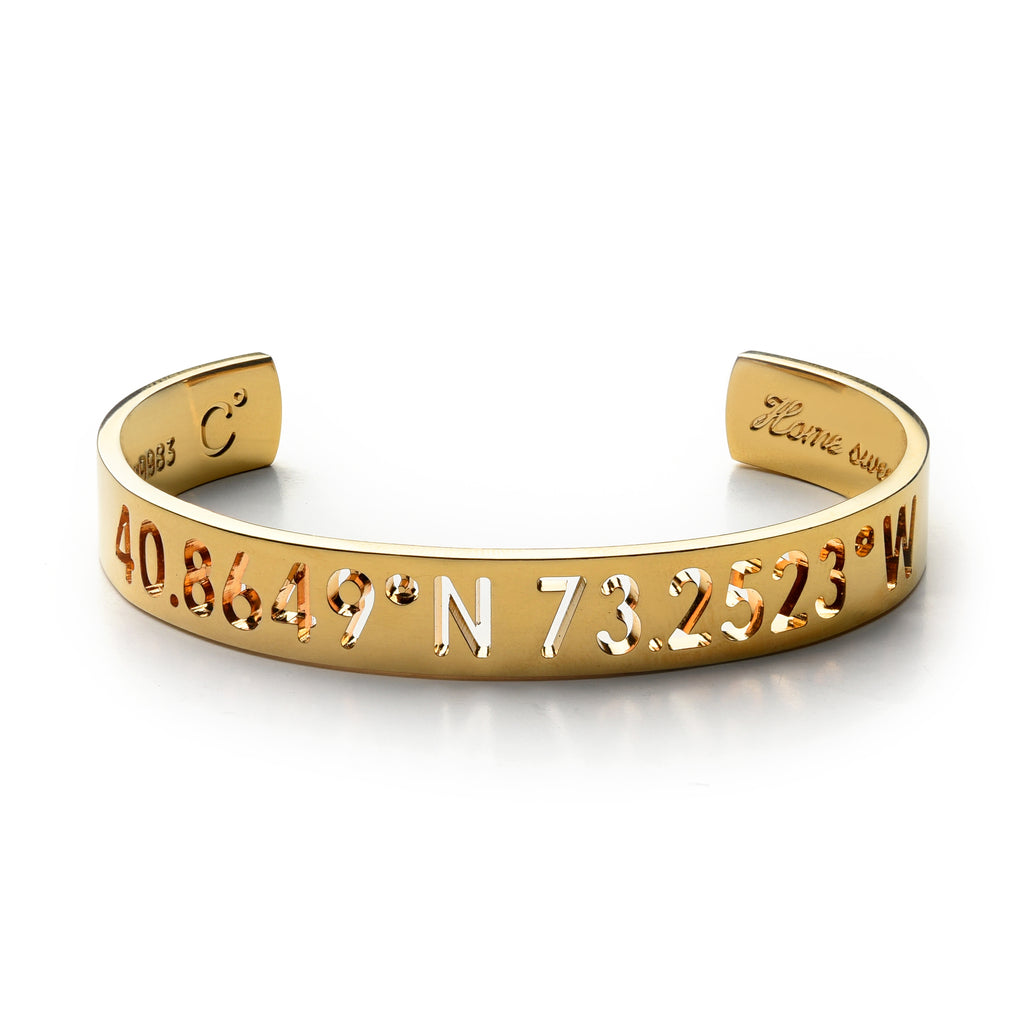 A gold cuff bracelet with carved out inscription