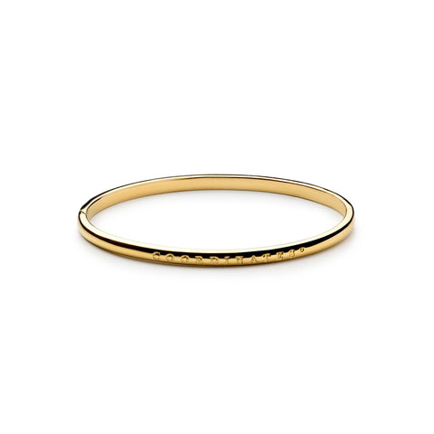 A delicate gold round bracelet with an exterior and interior inscription