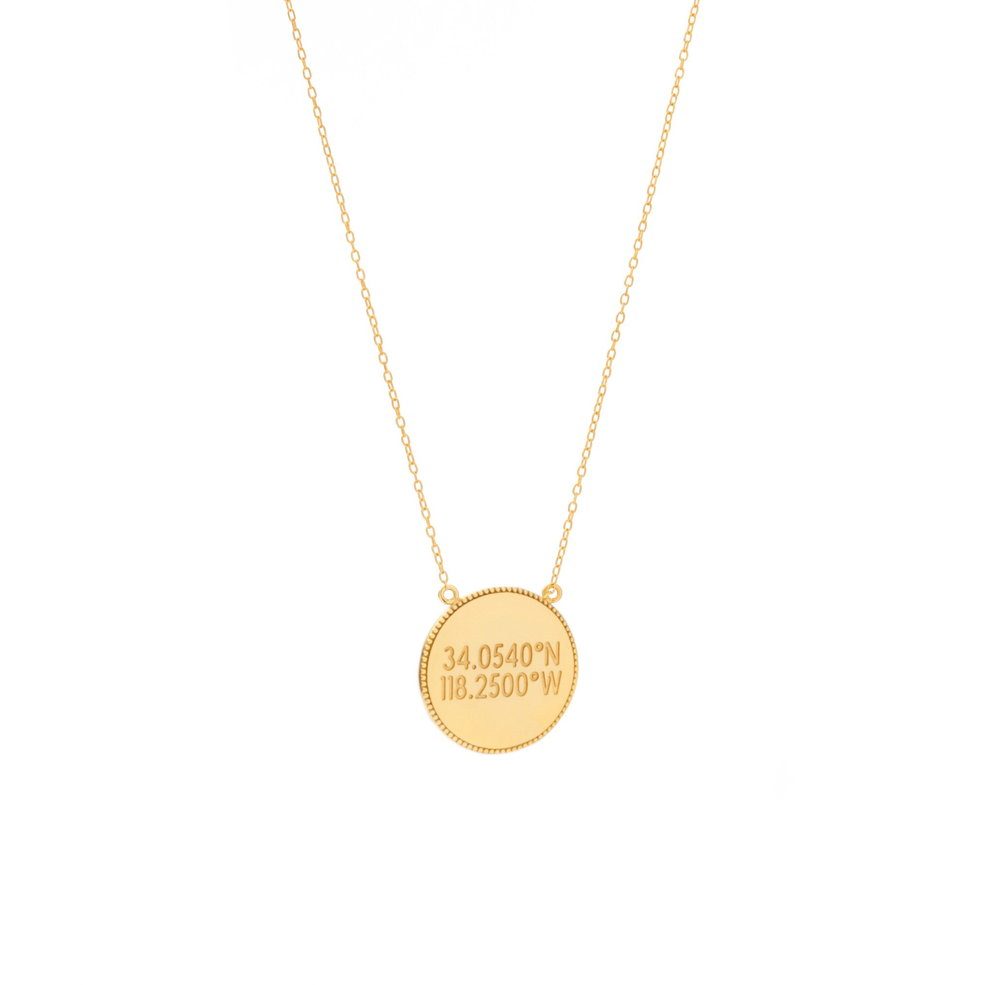 A flat circular gold pendant with inscription with scalloped edges on a gold chain