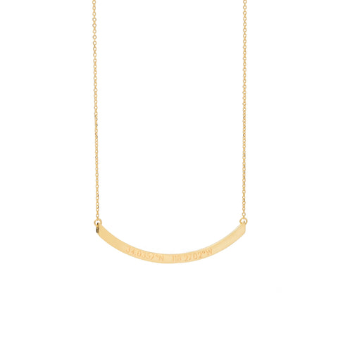 A long gold curved horizontal pendant with inscription on a gold chain