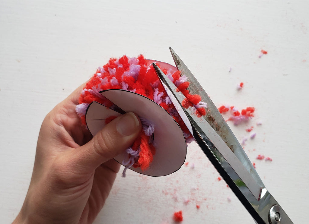 A pom pom is being trimmed with scissors