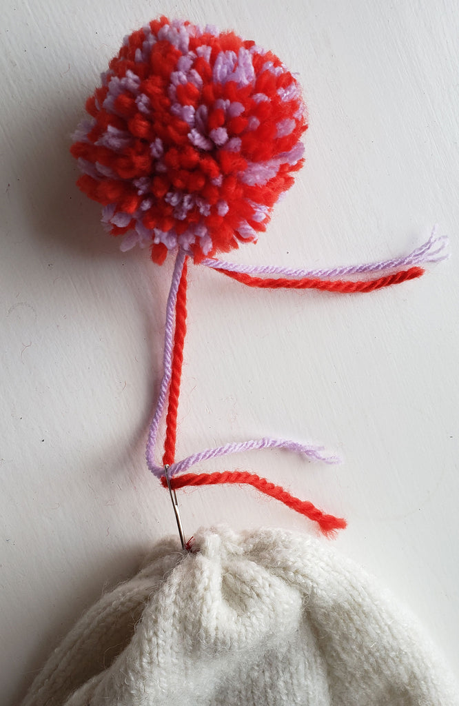 Reb and purple pom pom being attached by a hand sewing needle to the top of a winter hat