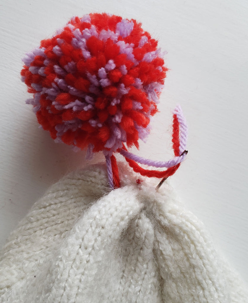 Yarn being sewn through to the wrong side of a winter hat, securing a pom pom