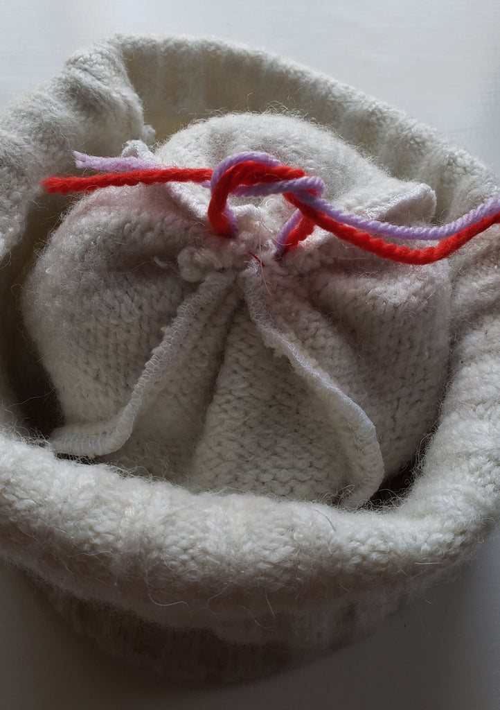 Knot being ties on the wrong side of a winter hat which will secure a pom pom